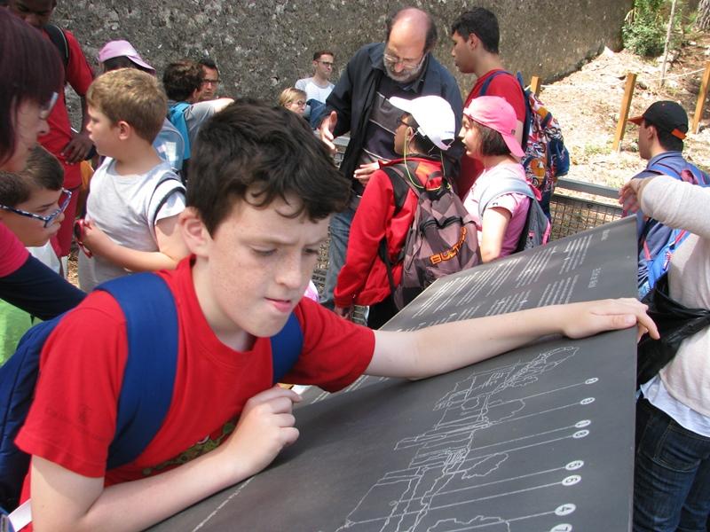 Alumnes de l'Escola Solc al mirador de la pedrera del Mèdol, escoltant el Jordi López (ICAC) i mirant el plafó explicatiu.