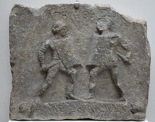 Marble relief with female gladiators, 1st-2nd century AD, from Halicarnassus (modern Bodrum, Turkey), British Museum (17590535705) by Carole Raddato is licensed under a Creative Commons Reconocimiento 4.0 Internacional License.Creado a partir de la obra en http://www.britishmuseum.org/explore/highlights/highlight_objects/gr/m/relief_female_gladiators.aspx.