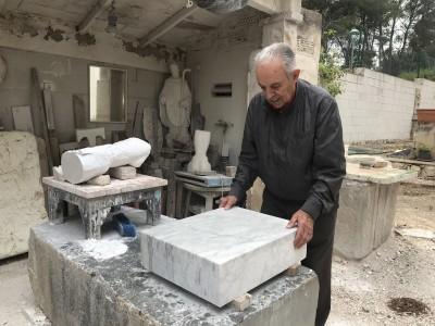 L'escultor Bruno Gallart treballant la peça de marbre amb què s'ha fet la reproducció de la pileta trilingüe. Foto: Museu Bíblic Tarraconense.