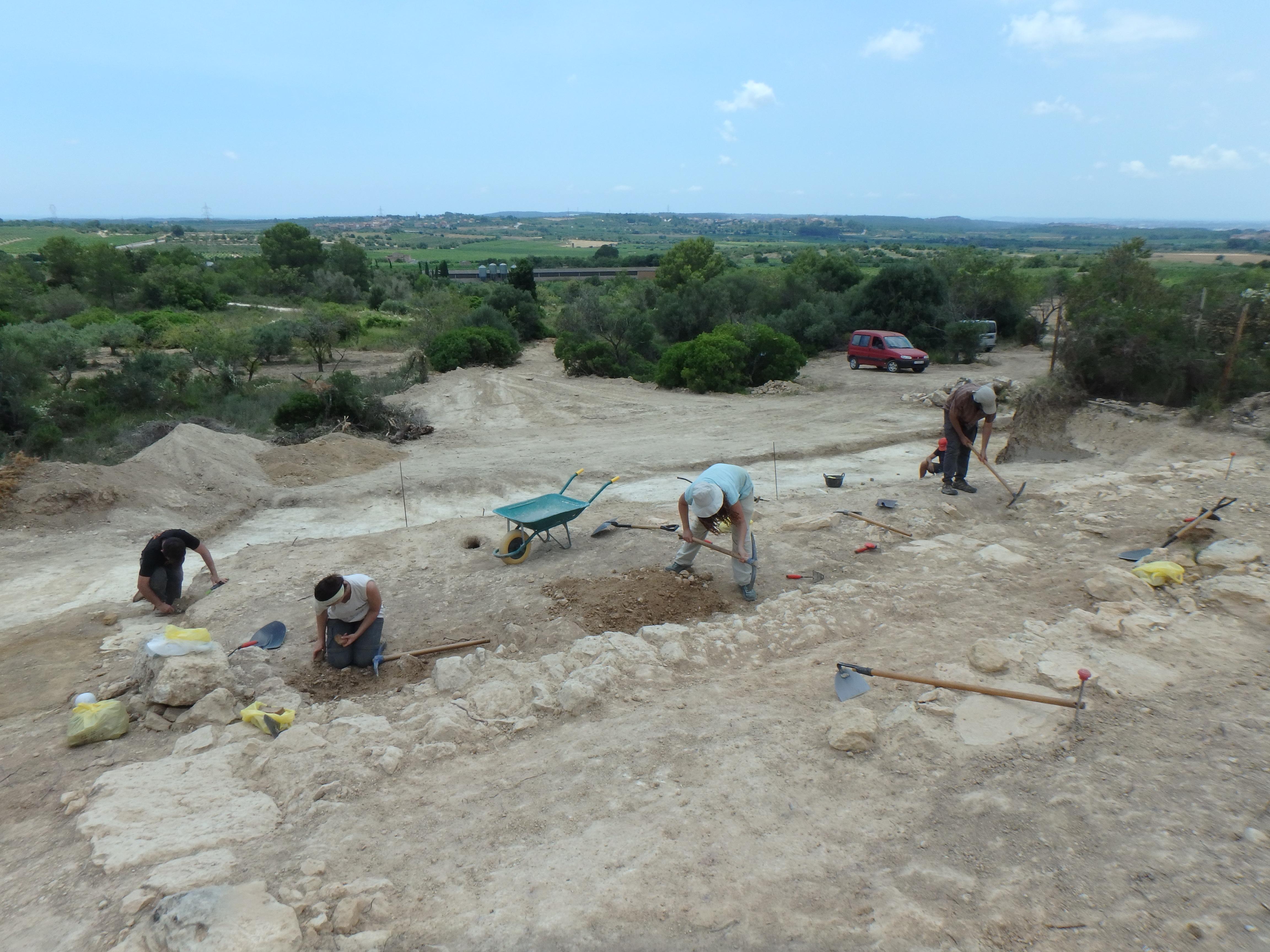 Els participants de la intervenció excavant entre els dos trams de muralla. Foto: ICAC