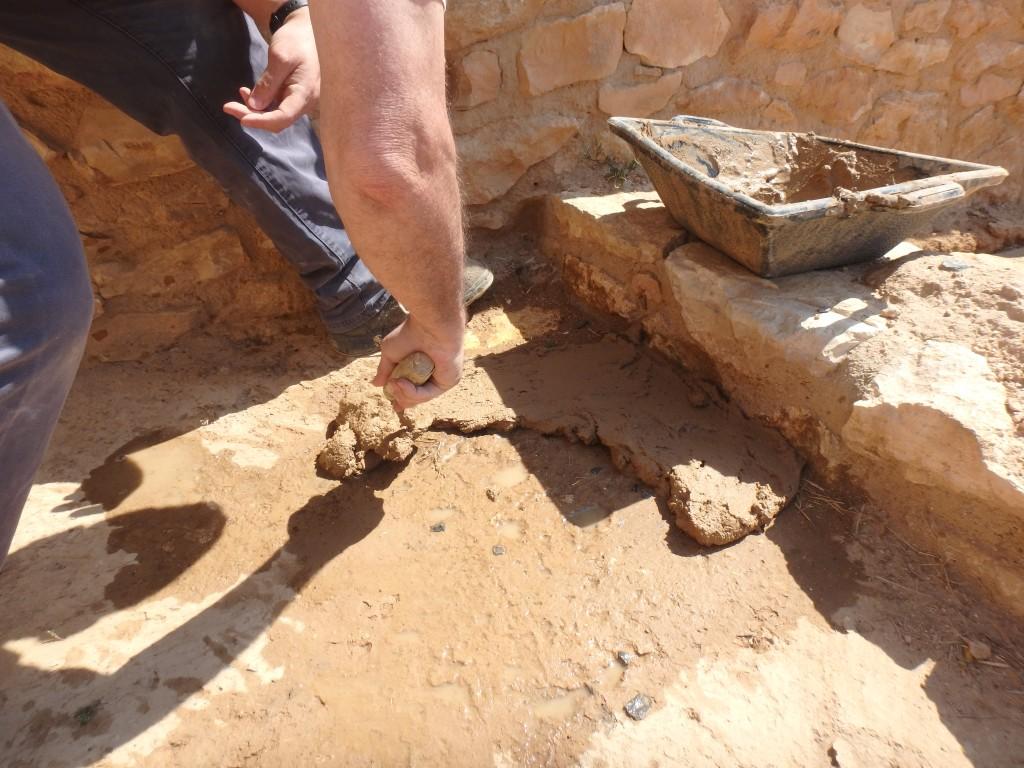 Construcció experimental d'una llar protohistòrica, en un espai exterior, fent servir una capa de fang dipositada directament sobre el sòl i en un espai exterior. Foto: projecte TRANSCOMB (ICAC).