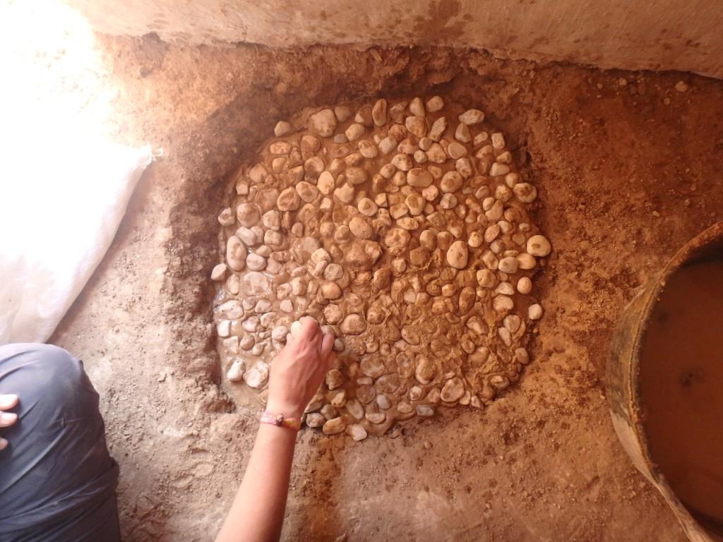 Construcció experimental d'una llar protohistòrica, en un espai interior, excavant una cubeta de pocs centímetres de fondària i reblerta amb capes de fang i còdols. Foto: projecte TRANSCOMB (ICAC).