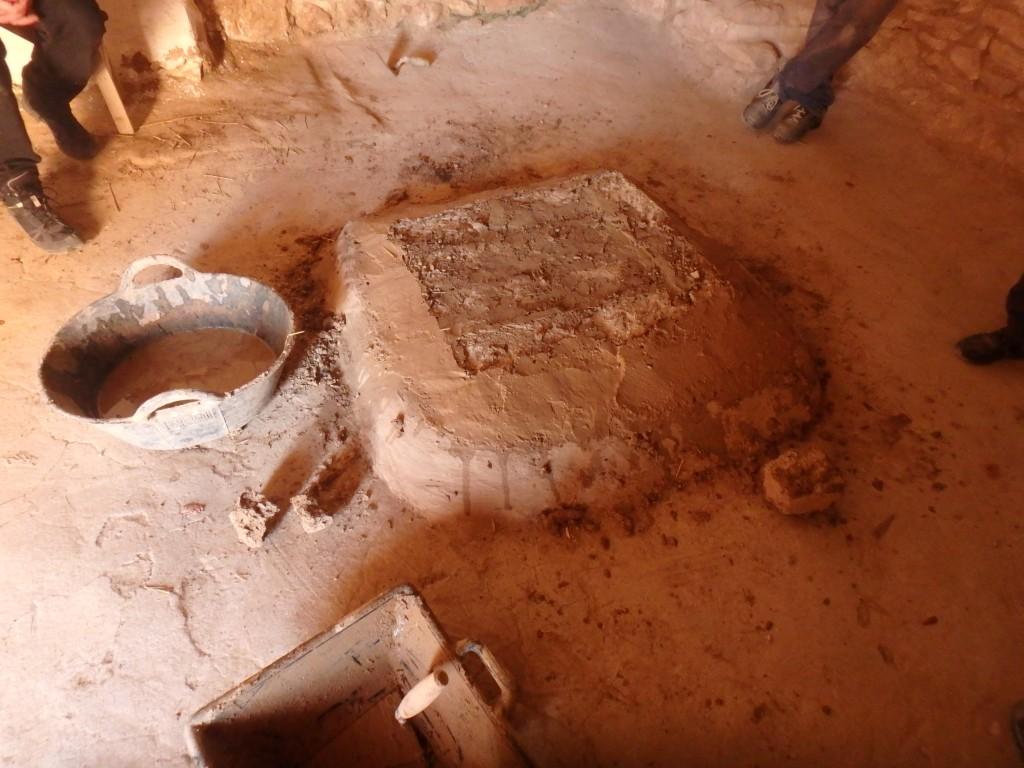 Imatge d'una llar construïda amb toves, en un espai interior, que quedasobreaixecadarespecte del nivell de paviment. Està delimitada per una revora, i el conjunt està revestit de fang. Foto: projecte TRANSCOMB (ICAC).