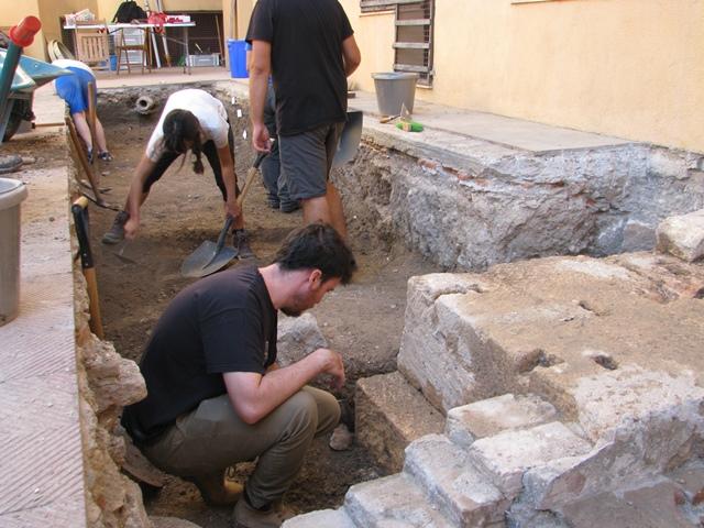 Intervenció arqueològica al pati del Museu Bíblic, amb la rasa que secciona el del mur de tancament dels porticats del recinte de culte imperial.