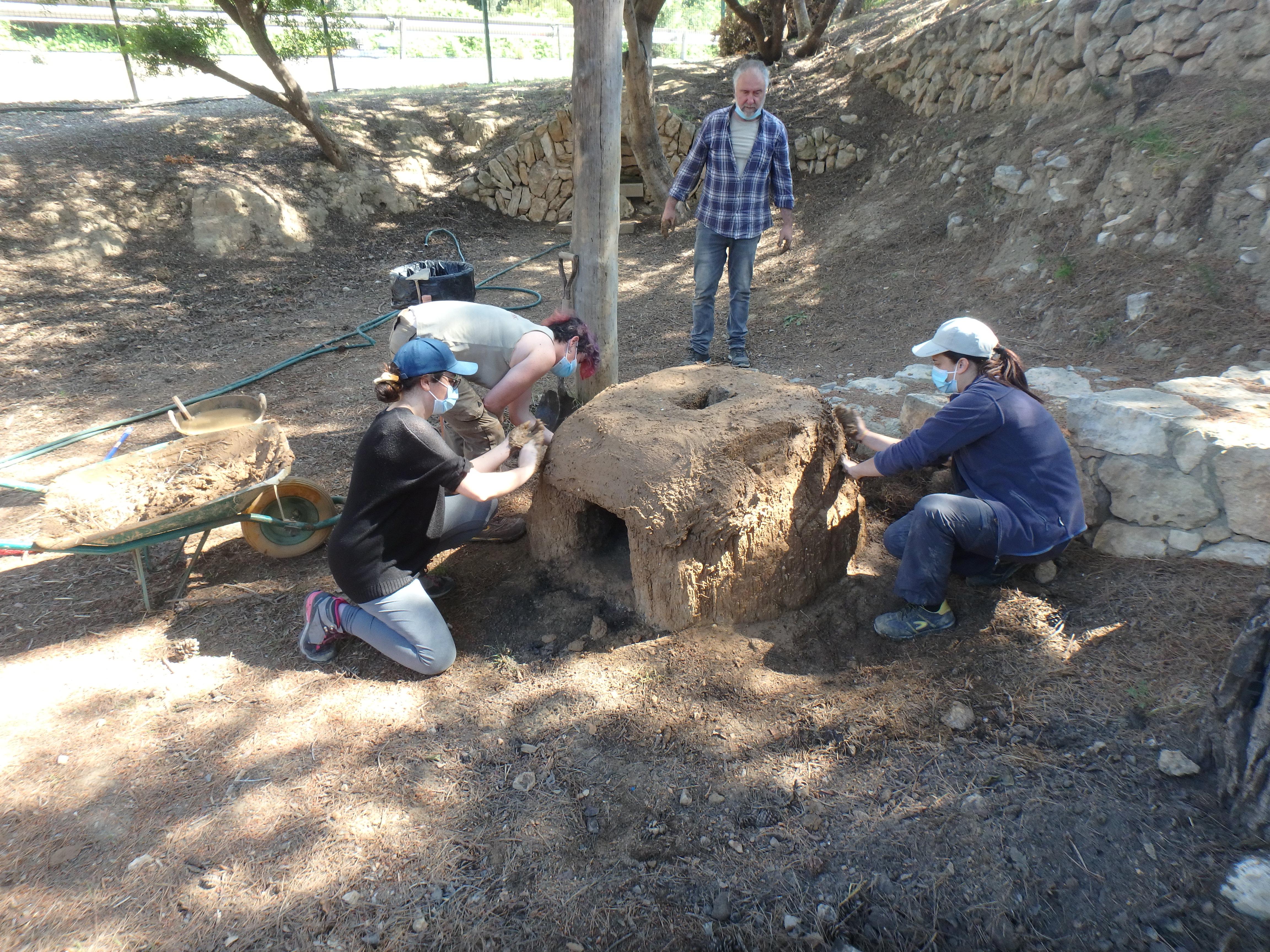 Construcció experimental d'un forn protohistòric, amb la volta construïda amb fang barrejat amb palla i sobre una base de fang, en espai exterior.Foto: projecte TRANSCOMB (ICAC).